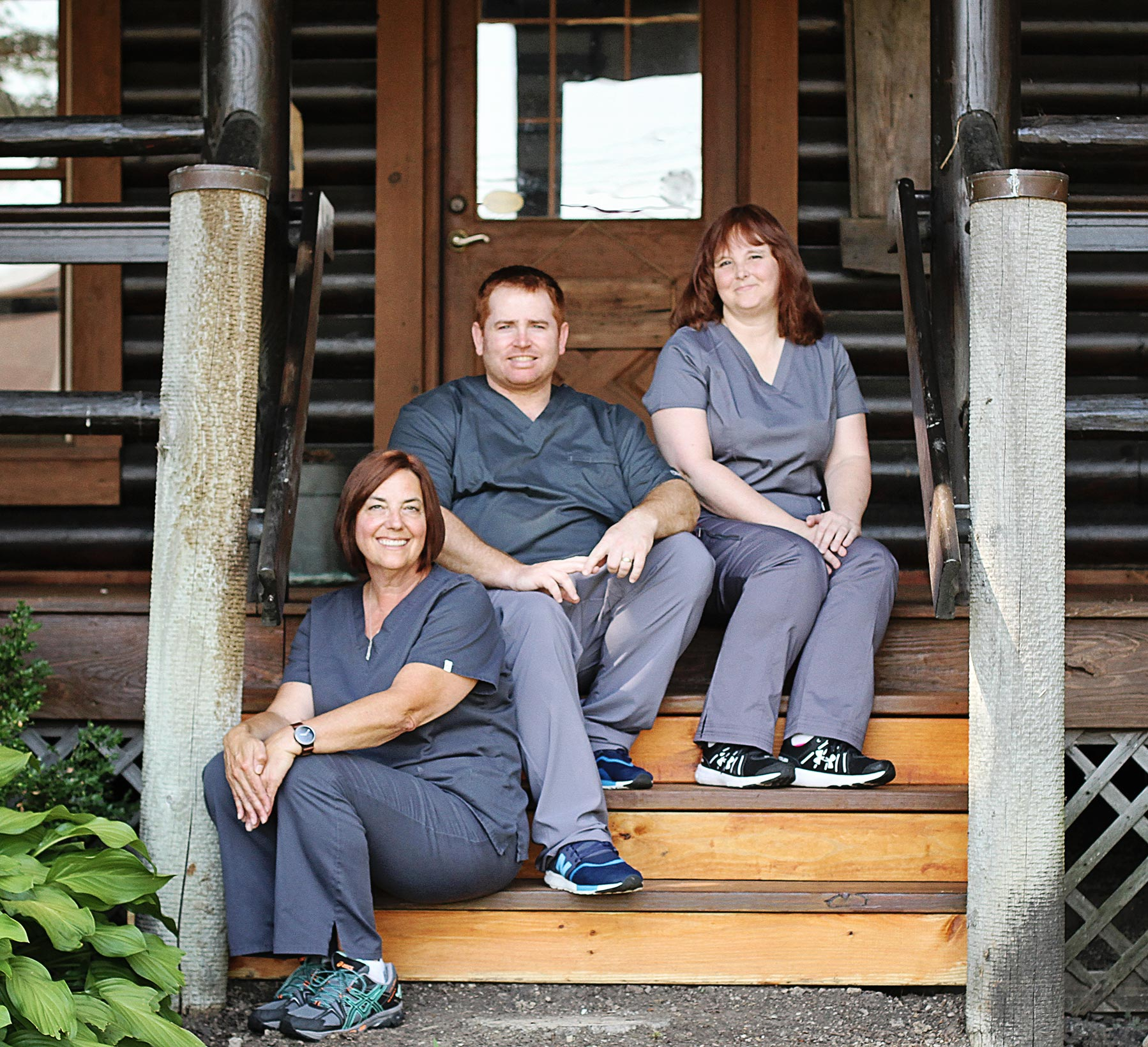 Dr. Kanetsky smiling in front of cabin with his staff